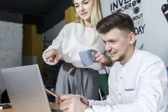 Obrazek biznesmena obsiadanie przy stołem Jest przyglądającym laptopu nad mienia ręką blisko go Dziewczyna stoi oprócz mężczyzny  zdjęcie royalty free