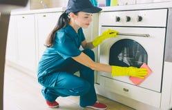 Obrazek czysty obsiadanie w oddział pozyci i płuczkowej kuchence Używa pomarańcze łachman Dziewczyna czyści bardzo dobrego Jest a fotografia stock