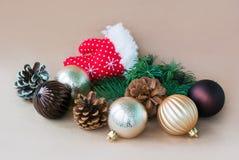Obrazek dekoracyjna rękawiczka Święty Mikołaj, sosna rożki i jedlinowa gałąź na beżowym backgroun wokoło której bawją się kłamstw zdjęcia royalty free