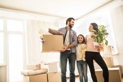 Obrazek dobra rodzinna pozycja w pokoju wpólnie Rodzice są przyglądający each ono uśmiecha się i inny Mężczyzna trzyma pudełko zdjęcie stock