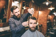 Obrazek dwa brodatego faceta jest w zakładzie fryzjerskim Fryzjer ciie włosy jego klient używa nożyce fotografia stock