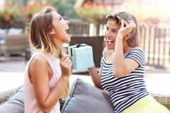 Obrazek dwa dziewczyna przyjaciela robi niespodzianka prezentowi urodzinowemu zdjęcia stock
