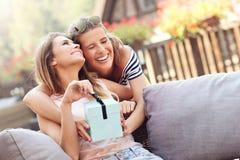 Obrazek dwa dziewczyna przyjaciela robi niespodzianka prezentowi urodzinowemu zdjęcie stock