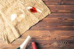 Obrazek dwa wino butelki wina szkła na pielusze na i brown, drewnianym tle, Zdjęcie Royalty Free
