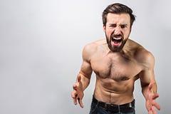 Obrazek facet bez koszulowej pozyci i wyrażać jego emocje Patrzeje prosto naprzód i wrzeszczeć Mężczyzna jest obrazy stock