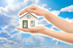 Obrazek kobiet ręki trzyma dom przeciw niebu Obraz Stock