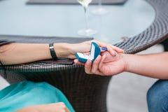 Obrazek mężczyzna kładzenia zobowiązania srebra pierścionek na kobiety ręce, plenerowy Obrazy Royalty Free
