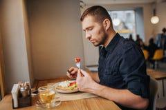 Obrazek mężczyzna obsiadanie przy łasowaniem i stołem Kawałek pomidor na rozwidleniu Facet jest przyglądający ja z poważnym Zdjęcie Royalty Free