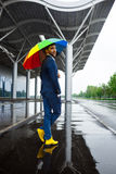 Obrazek młody biznesmen w kolorze żółtym kuje trzymać pstrobarwnego parasol w dżdżystej ulicie Fotografia Stock