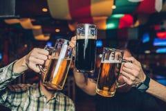 Obrazek młodzi człowiecy siedzi w pubie i trzyma kubki wpólnie zmrok i lekki piwo fotografia royalty free