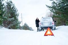 Obrazek młoda kobieta ma problem z samochodem na wint Obrazy Stock