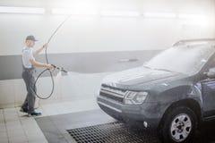 Obrazek pracownika czyści samochód Używa wodną kiść fo to Młody człowiek trzyma elastycznego węża elastycznego Jest poważny i fotografia royalty free