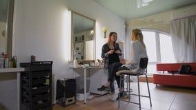 Obrazek pracujący dzień wśrodku piękna siedzi na krzesło klienta pięknej młodej kobiecie Makijażu artysta robi makijażowi w a zbiory wideo