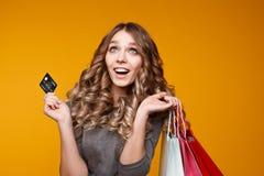 Obrazek rozochocona młoda brunetki kobieta w białej lato sukni mienia karcie kredytowej pozuje z torbami na zakupy i zdjęcia stock