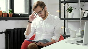 Obrazek rozochocony biznesmena obsiadanie w biurze podczas gdy pisać notatce patrzeć kamerę 4K zbiory wideo