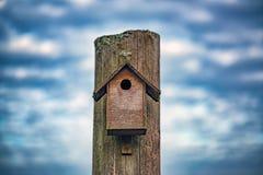 Obrazek stary drewniany ptaka dom z dramatycznym niebieskiego nieba ath tło obrazy royalty free