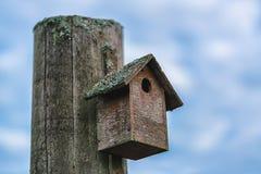 Obrazek stary drewniany ptaka dom z dramatycznym niebieskiego nieba ath tło zdjęcie royalty free