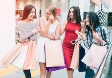 Obrazek szczęśliwe i zadowolone kobiety iść wpólnie Są w sklepie Dziewczyny są przyglądającym each inny i śmiać się obrazy royalty free