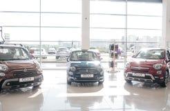 Obrazek trzy ładnego Fiat samochodu stoi wśrodku handlarskiego salonu z szklanymi ścianami Ja jest jaskrawym outsode i inside tak zdjęcia royalty free