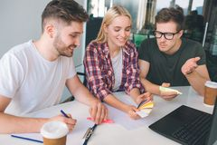 Obrazek trzy coworkers siedzi wpólnie przy stołem w pokoju Młoda kobieta chwyta koloru spojrzenie przy nim i paleta facet jeden zdjęcie royalty free