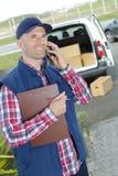 Obrazka deliveryman mienia szczęśliwy pudełko i telefon komórkowy fotografia royalty free