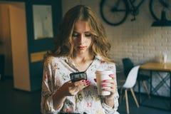 _obrazować potomstwo śliczny blondynka dziewczyna z filiżanka kawy mienie dzwonić i typing tekst, piękny yong kobieta z jaskrawy fotografia stock