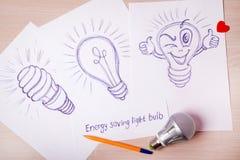 Obrazuje pióro Energooszczędną żarówkę na białym papierze Zdjęcie Royalty Free
