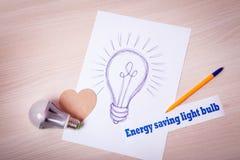 Obrazuje pióro Energooszczędną żarówkę na białym papierze Zdjęcia Stock