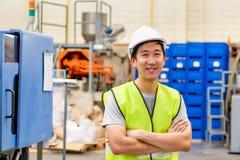Obrero sonriente con seguridad dif?cilmente en instalaciones industriales imágenes de archivo libres de regalías