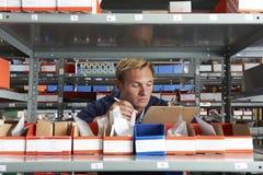 Obrero In Store Room que comprueba la acción Fotos de archivo libres de regalías