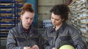 Obreros de sexo femenino que examinan documentos juntos en el almacenamiento fotos de archivo libres de regalías