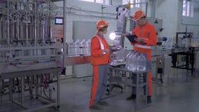 Obreros hombre y hembra en casco y guardapolvo cerca de la línea del transportador para embotellar el agua mineral en botellas pl almacen de video