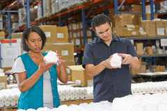 Obreros que controlan mercancías en cadena de producción imagen de archivo