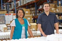 Obreros que controlan mercancías en cadena de producción Foto de archivo libre de regalías