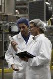 Obreros que examinan el agua embotellada en la planta de embotellamiento Imagen de archivo libre de regalías