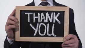Obrigado escrito no quadro-negro nas mãos do homem de negócios, apreciação da doação video estoque