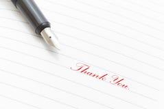 Obrigado escrito no vermelho em um papel Imagens de Stock Royalty Free