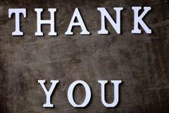 Obrigado exprimir das letras de madeira brancas na tabela e nas mãos imagens de stock