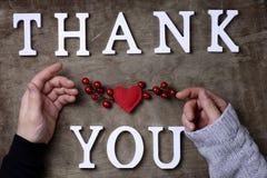 Obrigado exprimir das letras de madeira brancas na tabela e nas mãos fotografia de stock