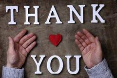 Obrigado exprimir das letras de madeira brancas na tabela e nas mãos fotos de stock