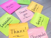 Obrigado mensagem em l?nguas diferentes na nota da etiqueta no fundo de madeira fotografia de stock royalty free