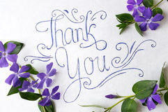 Obrigado notar cercado por flores roxas imagens de stock royalty free