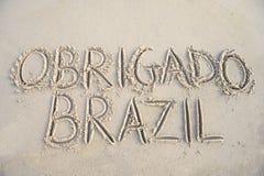 Obrigado tackar dig det Brasilien meddelandet i sand Arkivfoto