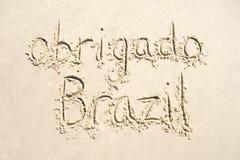 Obrigado tackar dig det Brasilien meddelandet i sand Fotografering för Bildbyråer