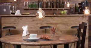 Obruszenie strzelał od prawej do lewej sklepu z kawą stół z filiżanka kawy na nim zdjęcie wideo