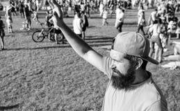 Obsługuje brodatego modnisia przed tłum zieleni pola tła ludźmi Miastowy wydarzenia świętowanie Mężczyzna falowania ręki słoneczn obraz royalty free