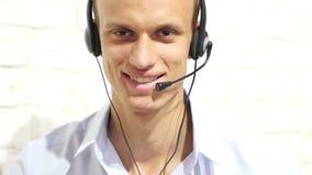 Obsługa klienta przedstawiciel jest ubranym słuchawki przy biurem, centrum telefoniczne zbiory wideo