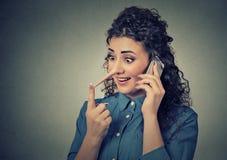 Obsługi klienta kłamca z długim nosem Kobieta opowiada na telefonie komórkowym mówi kłamstwa zdjęcia royalty free