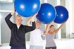 Obsługuje ćwiczyć z gym piłką w sprawności fizycznej centrum Obrazy Royalty Free