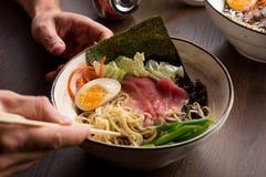 Obsługuje łasowań Azjatyckich ramen z tuńczykiem i kluskami w restauracji obraz stock